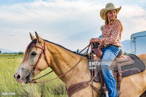 Porträt einer glückliche junge Cowgirl auf dem Pferderücken