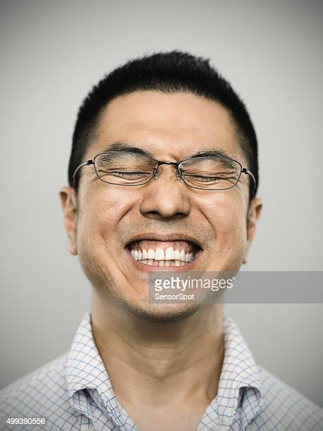 Portrait of a happy young japanese man looking at camera