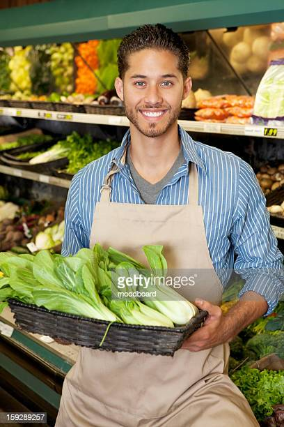 portrait of a happy young salesperson with bok choy in market - 白梗菜 ストックフォトと画像