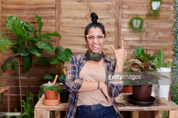 portrait of a happy young woman gardening on her terrace - jardinier humour photos et images de collection