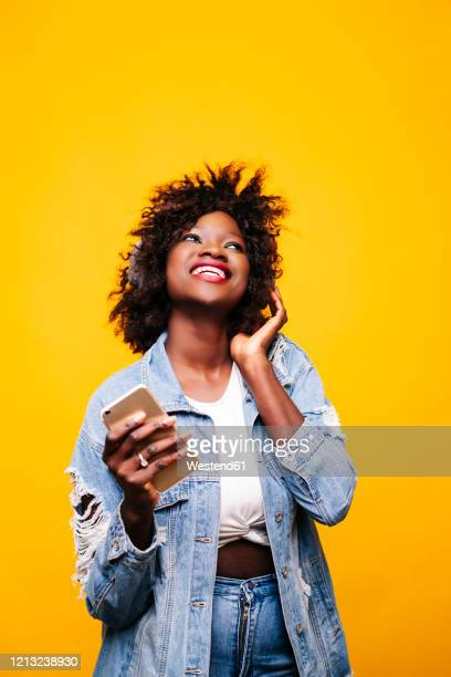 portrait of a happy young woman in studio with smartphone and headphones - bright colour stock pictures, royalty-free photos & images
