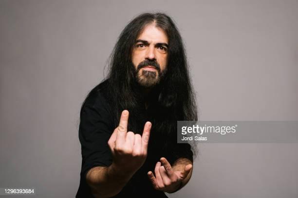 portrait of a heavy metal man doing rock symbol with his hands - heavy metal stock-fotos und bilder