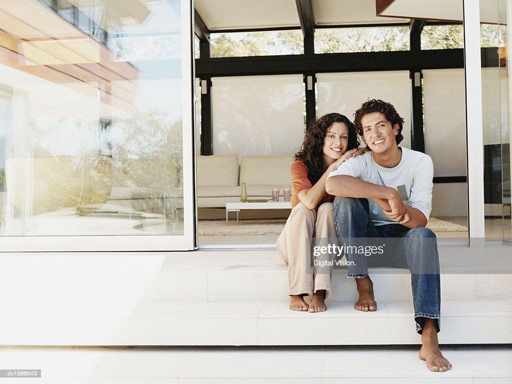 Portrait of a Heterosexual Couple Sitting by Patio Doors : Stock Photo