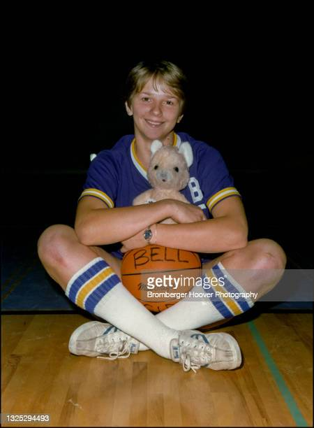 Portrait of a high school basketball player, seated cross-legged on the floor, with a basketball and teddy bear in her lap, Los Angeles, California,...