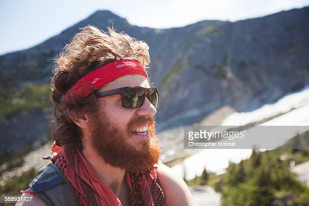 Portrait of a hiker wearing a bandana and sporting a thick beard.