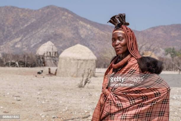 Portrait of a Himba woman in her village of mud huts. Himbas are a bantu tribe who migrated into what today is Namibia a few centuries ago. They...