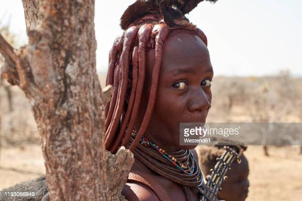 portrait of a himba woman sticking out tongue, opuwo, namibia - himba stock-fotos und bilder
