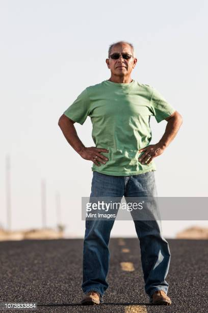a portrait of a hip senior hispanic male on a road trip. - arms akimbo stock pictures, royalty-free photos & images