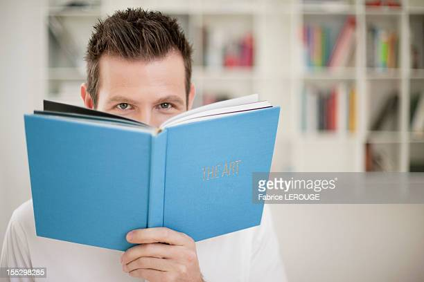 Portrait of a holding a book in front of his face