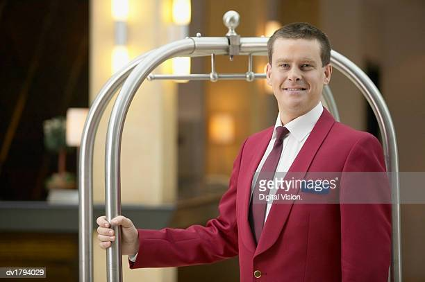 portrait of a hotel doorman in uniform standing next to a trolley - doorman stock photos and pictures