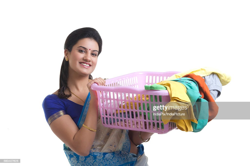 Portrait of a housewife holding a laundry basket : Stock Photo