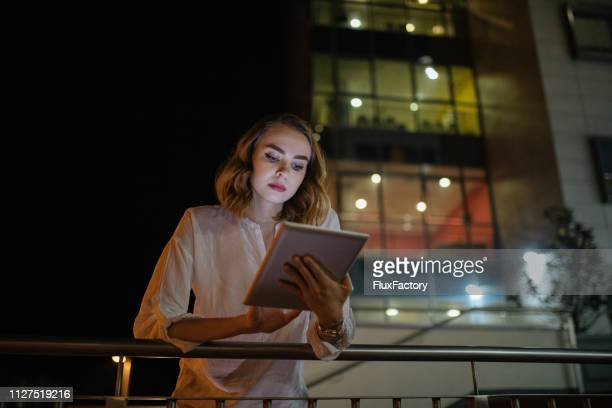 portrait of a human resources manager working on her digital tablet outside her office - managing director stock pictures, royalty-free photos & images