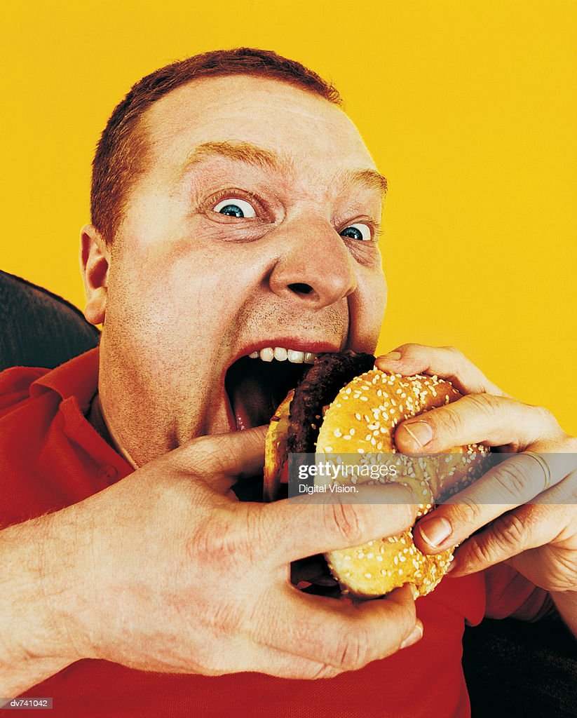 Portrait of a Hungry Man Eating a Hamburger : Stock Photo