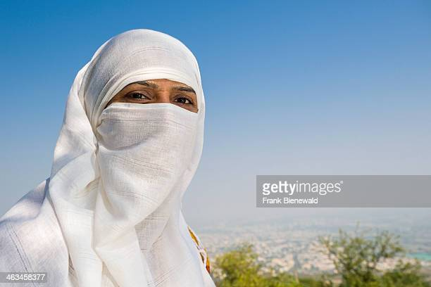 A portrait of a Jain pilgrim woman covering her face with a white cloth and walking the 3500 steps up to Shatrunjaya hill Shatrunjaya is one of the...