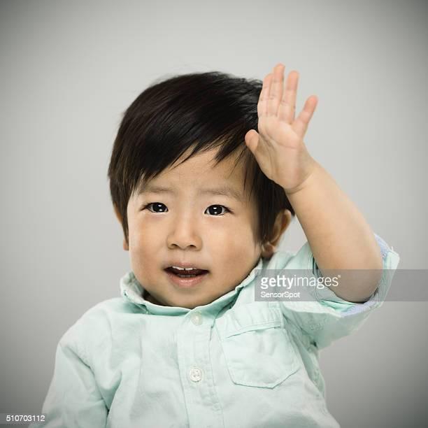 Porträt von einem japanischen Baby Erhöhung seiner Hand.