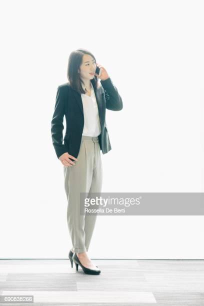 スマート フォンと日本のビジネス女性のポートレート - スマートカジュアル ストックフォトと画像