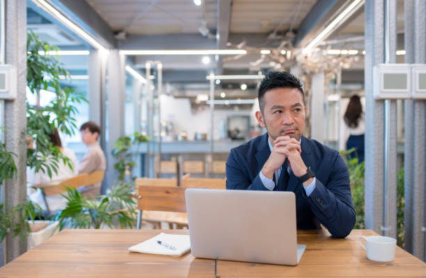portrait of a japanese businessman using his laptop - asain office man stock pictures, royalty-free photos & images