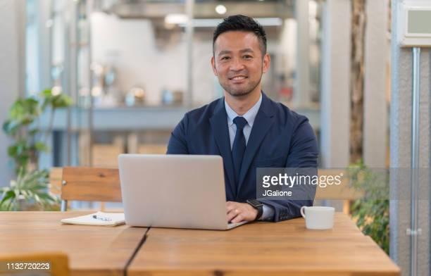 Portrait of a Japanese Businessman using his laptop