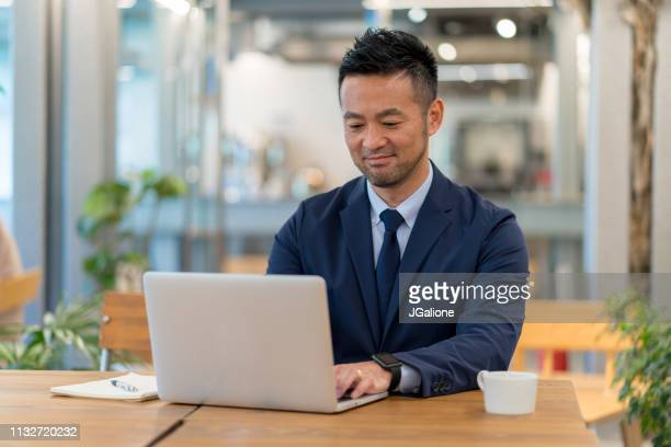 portrait of a japanese businessman using his laptop - jgalione stock pictures, royalty-free photos & images