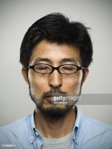 Portrait of a japanese man with closed eyes wearing glasses