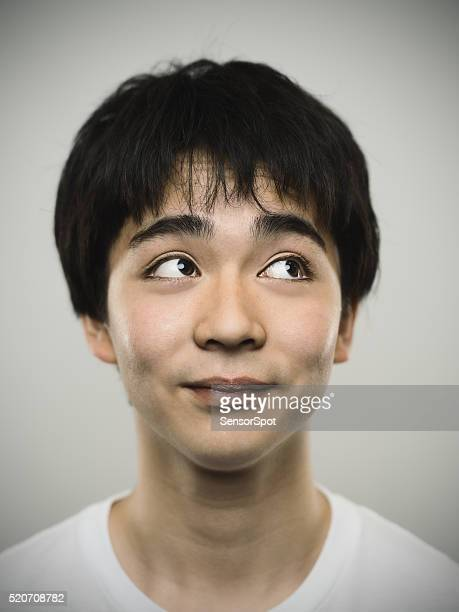 Portrait of a japanese teenager looking up.