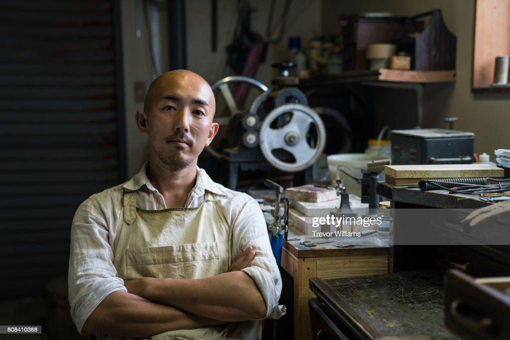 Portrait of a jewellery artist in his metal working workshop : Stock Photo