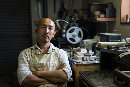 Portrait of a jewellery artist in his metal working workshop - gettyimageskorea