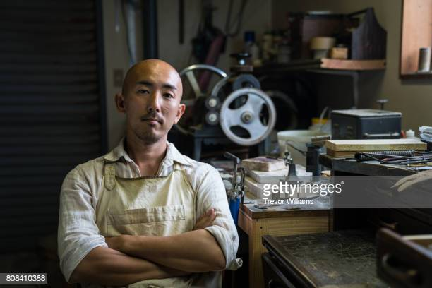 Portrait of a jewellery artist in his metal working workshop
