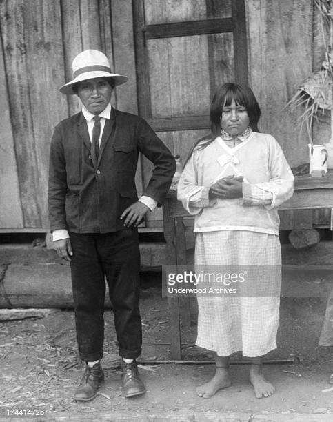Portrait of a Jivaro headhunter and his wife all dressed up and awaiting a visit from the Padre Superior Ecuador 1926