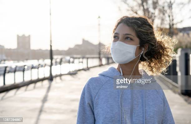portrait of a jogger wearing a facemask outdoors in london - state of emergency stock pictures, royalty-free photos & images