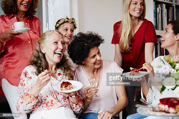 portrait of a joyful group at a party eating cake and having fun
