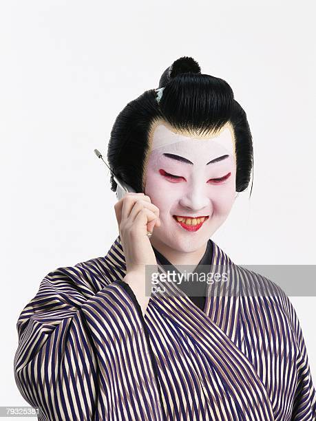 Portrait of a Kabuki actor talking on mobile phone and smiling, Front View
