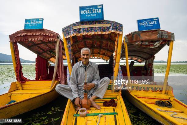 portrait of a kashmiri man with his shikara (traditional boat) in kashmir, india. - shaifulzamri - fotografias e filmes do acervo