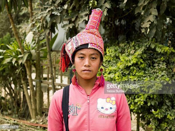 Portrait of a Ko Pala ethnic minority woman wearing a traditional headdress and Hello Kitty modern sweatshirt at Pak Nam Noi market Phongsaly...