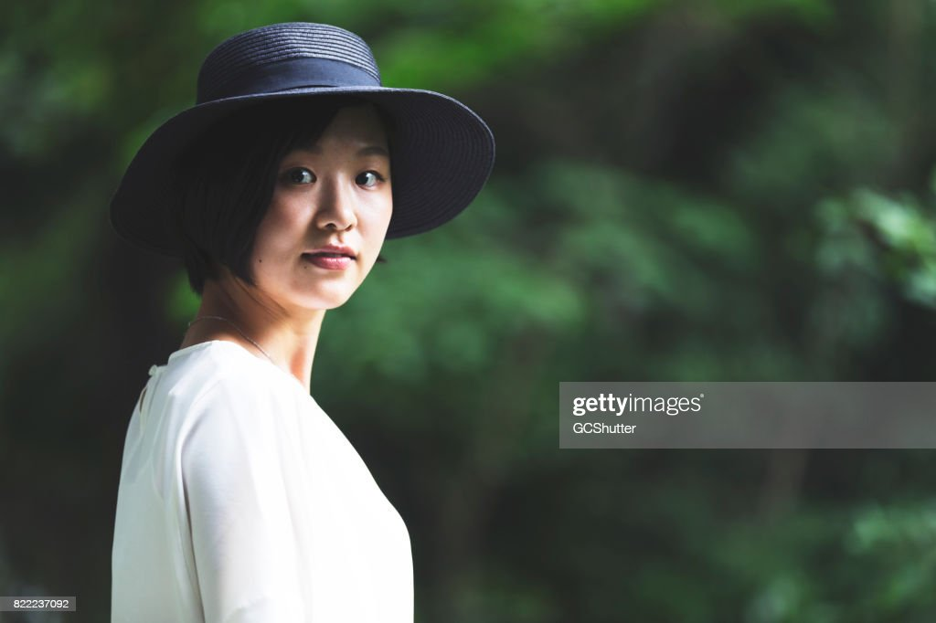 Portrait of a Korean women in front of a green background : Stock Photo