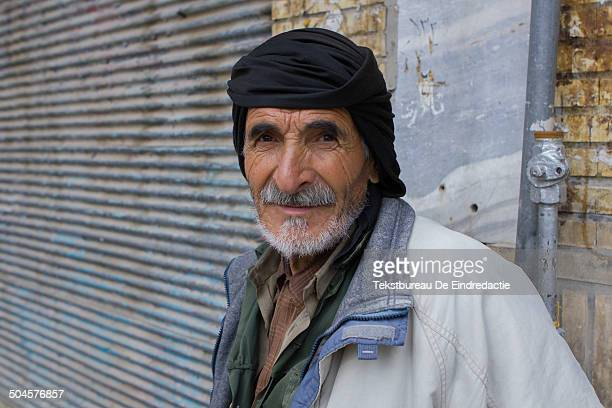 CONTENT] Portrait of a KurdishIranian man with a white beard wearing a black turban posing in front of a closed shop on the streets of Sanandaj...