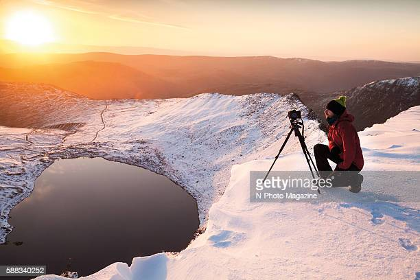 Portrait of a landscape photographer with a tripodmounted DSLR taking pictures of the sunrise on the peak of Helvellyn in the Lake District on May 1...
