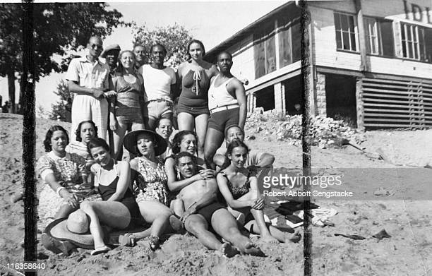 Portrait of a large group of unidentified people as they pose on the beach outside the Idlewild Club House Idlewild Michigan September 1938 Idlewild...