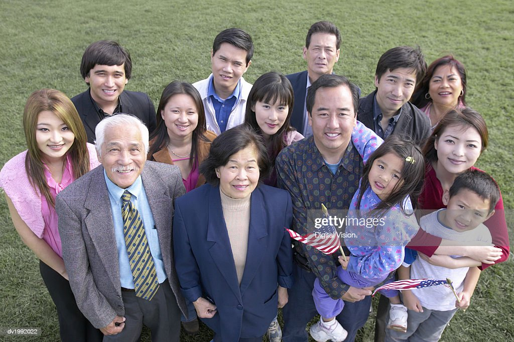 Portrait of a Large Multi Generational Family, with the Children Holding Stars and Stripes Flags : Stock Photo
