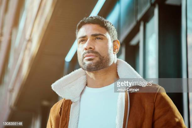 portrait of a latin man in an aviator jacket, looking away. serious expression. with a street buildings background. latins, models and fashion concept. - editorial stock pictures, royalty-free photos & images
