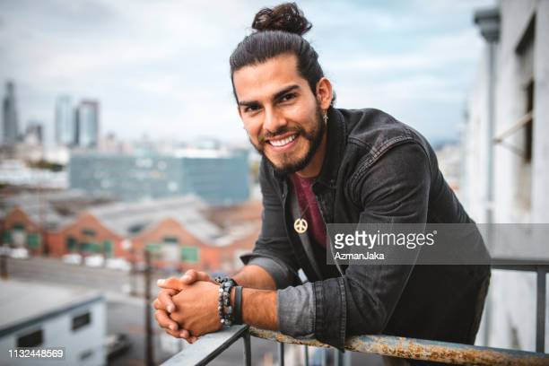 portrait of a latin man smiling and looking in camera - man bun stock pictures, royalty-free photos & images