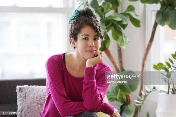 portrait of a latinx millennial woman with dyed blue hair, sits on a couch wearing a pink colored sweater. - millennial pink stock pictures, royalty-free photos & images