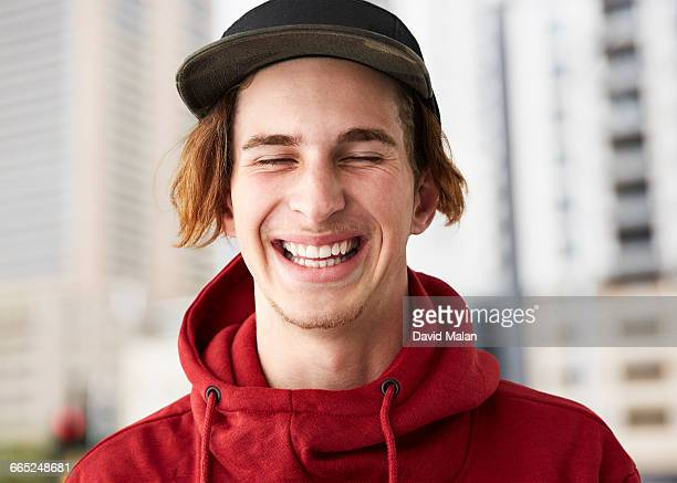 Portrait of a laughing young man in a red hoodie.