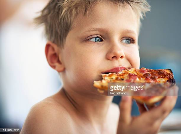 Portrait of a little boy eating pizza