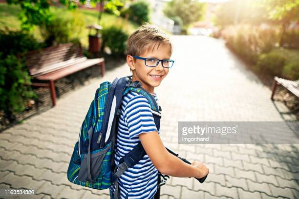 portrait of a little boy riding to school on push scooter - boys stock pictures, royalty-free photos & images