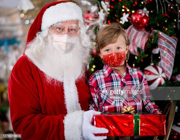 portrait of a little boy with santa wearing facemasks while getting a gift - father christmas stock pictures, royalty-free photos & images