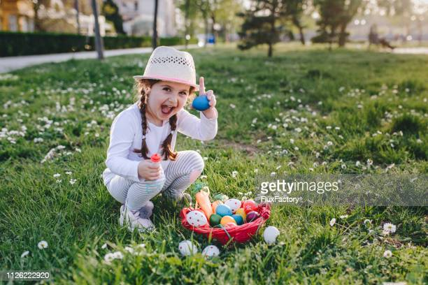 portrait of a little four year old girl holding an egg she found during an easter egg hunt - easter egg stock pictures, royalty-free photos & images