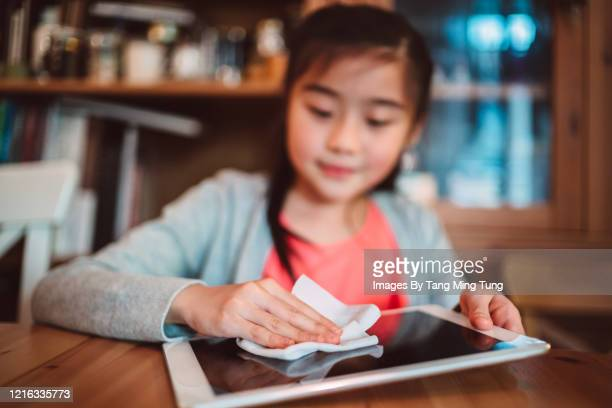 portrait of a little girl cleaning the surface of a digital tablet with disinfectant wipe at home - antiseptic wipe stock pictures, royalty-free photos & images