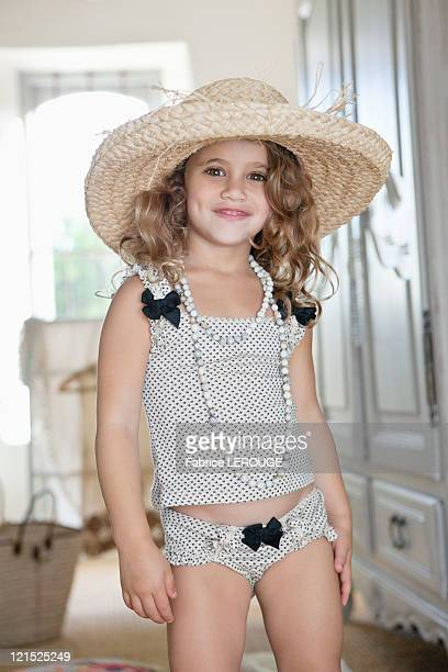 Portrait of a little girl dressed like her mother in oversized accessories