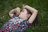 portrait little girl park sniffing flower